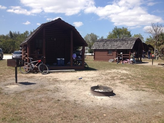 each cabin has a bar b q picnic table and a fire pit Oleta River State Park Cabins